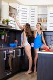 Retrato de dos hermanas gemelas que se divierten en la mañana que prepara el desayuno Imagenes de archivo