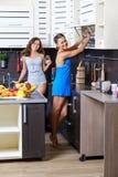 Retrato de dos hermanas gemelas que se divierten en la mañana que prepara el desayuno Imagen de archivo