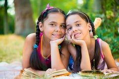Retrato de dos hermanas hispánicas que leen en el parque Imágenes de archivo libres de regalías