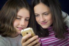 Retrato de dos hermanas lindas que miran el teléfono celular Fotos de archivo