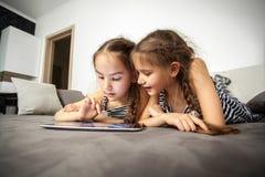 Retrato de dos hermanas que mienten en cama con la tableta Fotos de archivo