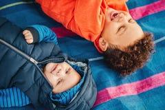 Retrato de dos hermanos divertidos que juegan afuera Imágenes de archivo libres de regalías