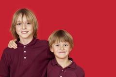 Retrato de dos hermanos felices contra fondo rojo Foto de archivo libre de regalías