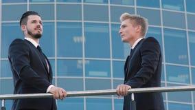 Retrato de dos hombres de negocios que se colocan en terraza y que discuten su negocio metrajes