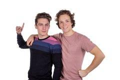Retrato de dos hombres jovenes felices que señalan los fingeres aislados sobre el fondo blanco imagenes de archivo