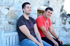 Retrato de dos hombres jovenes hermosos que se sientan en un banco y una risa Imagenes de archivo