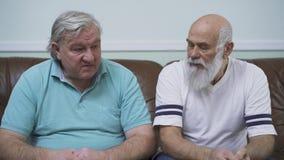 Retrato de dos hombres mayores maduros que se sientan en el sofá de cuero La gente feliz que charla, hablando, tiene conversación almacen de video