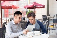 Retrato de dos hombres de negocios asiáticos que trabajan con la tableta en el caf fotos de archivo libres de regalías