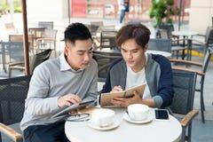 Retrato de dos hombres de negocios asiáticos que trabajan con la tableta en el caf foto de archivo libre de regalías