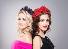 Retrato de dos magníficos, mujeres sonrientes que llevan el bijouterie de la flor Imagen de archivo libre de regalías