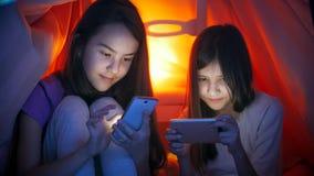 Retrato de dos muchachas adolescentes que usan smartphones debajo de la manta en el dormitorio Fotografía de archivo libre de regalías