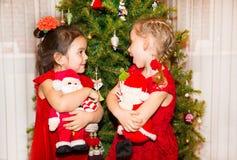 Retrato de dos muchachas de los niños alrededor de un árbol de navidad adornado Niño en Año Nuevo del día de fiesta Imágenes de archivo libres de regalías