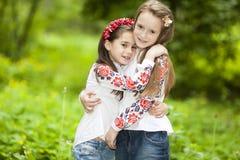 Retrato de dos muchachas en el parque en un fondo del árbol verde Fotos de archivo libres de regalías
