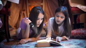 Retrato de dos muchachas en los pijamas que mienten en piso en la noche con el libro grande imagenes de archivo
