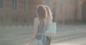 Retrato de dos muchachas felices que discuten las últimas noticias del chisme mientras que camina en una calle de la ciudad almacen de video