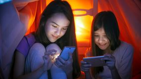 Retrato de dos muchachas lindas en pijamas con los teléfonos móviles en la noche Fotografía de archivo