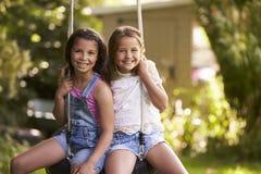 Retrato de dos muchachas que juegan en el oscilación del neumático en jardín Fotos de archivo