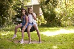 Retrato de dos muchachas que juegan en el oscilación del neumático en jardín Imágenes de archivo libres de regalías