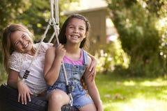 Retrato de dos muchachas que juegan en el oscilación del neumático en jardín Imagen de archivo libre de regalías