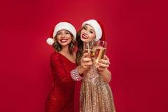 Retrato de dos muchachas sonrientes felices en vestidos brillantes Foto de archivo