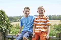 Retrato de dos muchachos que se sientan en la puerta junto Imágenes de archivo libres de regalías