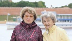 Retrato de dos mujeres adultas sonrientes al aire libre almacen de metraje de vídeo