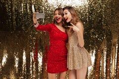 Retrato de dos mujeres bastante felices en vestidos brillantes Fotografía de archivo