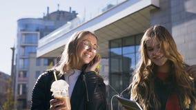 Retrato de dos mujeres caucásicas jovenes que usan la tableta digital y sonriendo feliz mientras que camina en centro de ciudad almacen de metraje de vídeo
