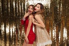 Retrato de dos mujeres emocionadas felices en vestidos brillantes Imagen de archivo