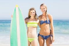 Retrato de dos mujeres en el bikini que se coloca con una tabla hawaiana en la playa Imágenes de archivo libres de regalías
