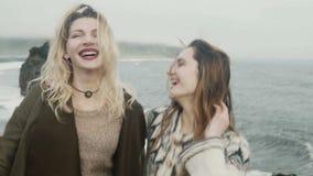 Retrato de dos mujeres felices que se unen en la playa negra en Islandia y que tienen la diversión, el salto y sonrisa metrajes