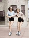 Retrato de dos mujeres jovenes con las cuchillas del rodillo que patinan en el camino y sonrisa (todas las personas representadas Imagen de archivo libre de regalías