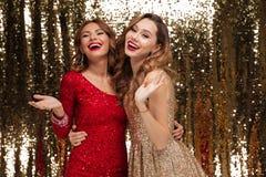 Retrato de dos mujeres jovenes felices en vestidos brillantes Fotografía de archivo