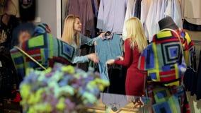 Retrato de dos mujeres jovenes hermosas que hacen compras en una tienda de ropa almacen de video