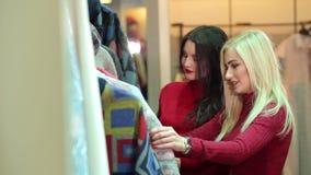 Retrato de dos mujeres jovenes hermosas que hacen compras en una tienda de ropa almacen de metraje de vídeo