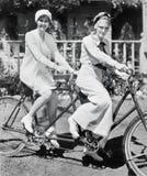 Retrato de dos mujeres jovenes que se sientan en una bicicleta del tándem (todas las personas representadas no son vivas más larg Fotos de archivo libres de regalías