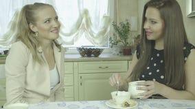 Retrato de dos mujeres jovenes sonrientes atractivas que comen té en la mesa de comedor almacen de metraje de vídeo