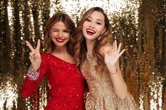 Retrato de dos mujeres sonrientes alegres en vestidos brillantes Fotografía de archivo libre de regalías
