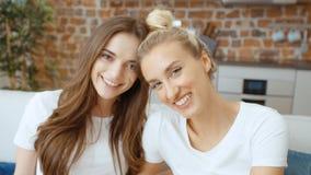 Retrato de dos novias adolescentes alegres que miran la cámara y la sonrisa metrajes
