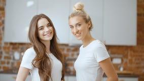 Retrato de dos novias adolescentes alegres que miran la cámara y la sonrisa almacen de metraje de vídeo