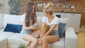 Retrato de dos novias adolescentes alegres que usan el teléfono en casa almacen de video