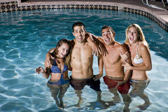 Retrato de dos pares en piscina en la noche Fotos de archivo