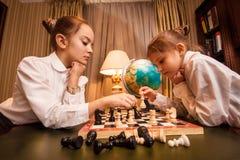 Retrato de dos pequeñas hermanas que juegan a ajedrez Imágenes de archivo libres de regalías