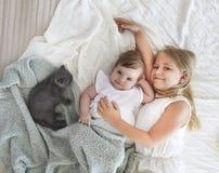 Retrato de dos pequeñas muchachas bonitas con el gatito Fotografía de archivo