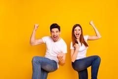 Retrato de dos personas extáticas locas alegres alegres encantadoras preciosas atractivas agradables que tienen buen triunfo de l imagen de archivo libre de regalías