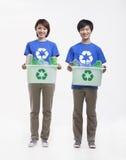 Retrato de dos personas jovenes sonrientes que sostienen las papeleras de reciclaje y que llevan reciclando las camisetas del símb Foto de archivo