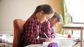 Retrato de dos tareas de escritura del adolescente en cuadernos de la escuela Imagenes de archivo