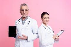 Retrato de doutores masculinos e fêmeas de sorriso com os estetoscópios que mantêm a tabuleta e a prancheta isoladas imagem de stock