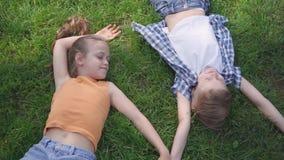 Retrato de duas crianças adoráveis bonitos que encontram-se na grama no parque que sorri entre si Menina engraçada que toma a mão filme