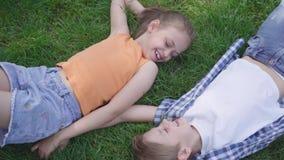 Retrato de duas crianças adoráveis engraçadas que encontram-se na grama no parque que sorri entre si A menina que toma a mão do vídeos de arquivo